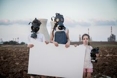 Save the planet. Young kids holding signs standing near a refinery with gas masks Stock Images