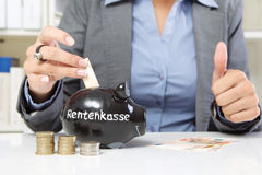 Save for retirement. Business woman putting money into black piggy bank with thumbs up Stock Photo