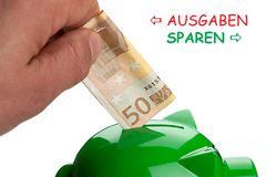 Save Spend in German. Hand putting banknote on a piggy bank and text Save Spend in German stock photo