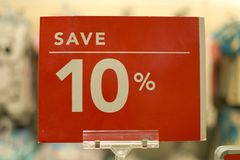 Save ten percent red sign board. Against a store background Royalty Free Stock Photos