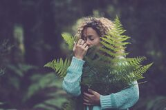 Free Save The Earth Planet And Celebrate Earth`s Day With Adult Woman Hug And Hold A Green Leaf In The Forest Wood Enjoying Nature - Stock Photo - 189077040