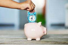 Save time concept with child's hand holding alarm clock over a ceramic piggy bank stock photo