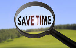 Save time. Magnifying glass with the word save time on blurred nature background. Searching save time concept Stock Photography