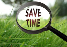 Save time. Magnifying glass with the word save time on grass background. Selective focus Royalty Free Stock Photo