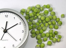 Save time on modern cooking. Save time clock and several green frozen beans royalty free stock image