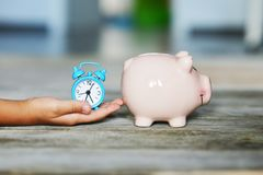 Save time for precious moment with your child concept, piggy bank and alarm clock in kid's hand royalty free stock photography