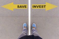 Save vs Invest text arrows on asphalt ground, feet and shoes on Royalty Free Stock Image