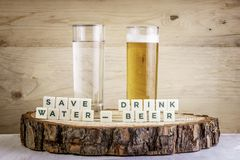 Save water drink beer - glass of water with glass of beer. Ecology concept. Save water, drink beer - glass of water with glass of beer. Ecology concept stock photos