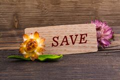 Save word. On wooden card with dried flower on wood royalty free stock images