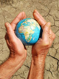 Save the world. Concept: earth supported by human hands on a dry land texture Stock Image