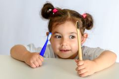 Little girl in white shirt holding bamboo toothbrush and plastic toothbrush. stock photography