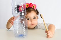 Little girl in white shirt holding bamboo toothbrush and plastic bottle. stock image