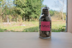 """Save"" Writing in the paper, Coins in a glass jar Stock Photography"