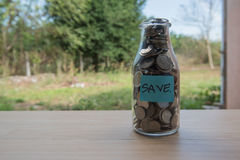 """Save"" Writing in the paper, Coins in a glass jar Royalty Free Stock Photography"