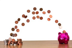 Save you Pennies. A stack of coins floating in mid air into a piggy bank stock photos