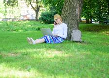 Save your time with shopping online. Sales manager occupation. Buy clothes online. Girl sit grass with notebook. Woman. With laptop in park order item on phone royalty free stock image