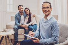 Professional family therapist helping his patients. Saved family. Professional family therapist taking notes while helping his patients stock photography