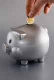 Saving. A man's hand putting a coin in the piggy bank royalty free stock photos