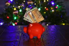 Saving for Christmas gifts. Piggy bank with euro notes. Saving for Christmas gifts. Sparschweinchen with euro notes stock image