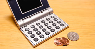 Saving Chump Change. Calculator with Quarter and Pennies for banking and financial presentations Stock Photos