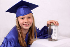 Saving for college. Young girl in graduation cap and gown with college savings jar Royalty Free Stock Photography