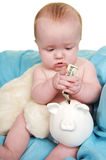 Saving for College. Up Close of cute baby putting money in a piggy bank Stock Photo