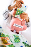 Saving concept. Child puts money in piggy bank. Selective focus Stock Photos