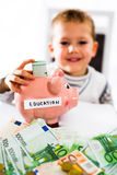 Saving concept. Child puts money in piggy bank. Selective focus Stock Images