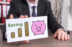 Saving concept on an index card. Businessman showing an index card with saving concept Royalty Free Stock Photos