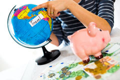 Saving concept. Piggy bank with an inscription travel. Woman holding a globe Stock Photos