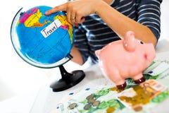 Saving concept. Piggy bank with an inscription travel. Woman holding a globe Stock Photos