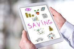 Saving concept on a tablet. Man holding a tablet showing saving concept Stock Photo