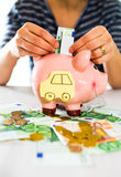 Saving concept. Women's hand puts money in piggy bank. Selective focus Royalty Free Stock Photography