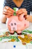 Saving concept. Women's hand puts money in piggy bank. Selective focus Royalty Free Stock Photo