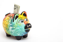 Saving dollars in a Colorful piggy bank. Side view Stock Photos