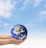 Saving Earth. Hands holding earth on a blue sky Stock Photo