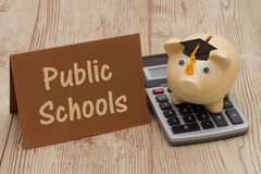 Saving on education by attending public schools. A golden piggy bank with grad cap on a calculator on a desk with text Public Schools Royalty Free Stock Images