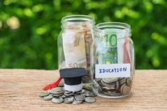 Saving for Education concept as coins in jar with text Education stock photos