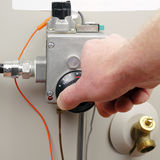 Saving Energy. Hand of a man turning down household gas water heater temperature Stock Photo