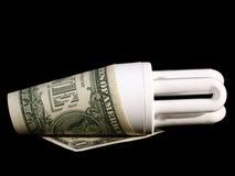 Saving Energy. An energy saving light bulb with a US dollar Royalty Free Stock Images