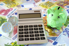 Saving energy with energy-saving lamps. Pocket calculator with blank display, LED lamps, green piggy bank on a background made of euro banknotes and coins Stock Images