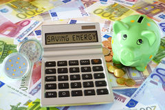 Saving Energy with LED Lamps. Pocket calculator with the words Saving Power, two LED lamps and a green piggy bank on a background made of Euro banknotes and Stock Image