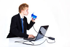 Saving the environment. Man charging power to the laptop by blowing into a fan Royalty Free Stock Images