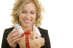 Saving Euro. Blonde business woman with piggy bank and European currency stock photo