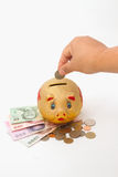 Saving, Female hand putting a coin into piggy bank for retiremen Stock Image