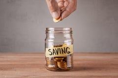 saving Frasco de vidro com moedas e uma economia da inscrição O homem guarda a moeda fotografia de stock royalty free
