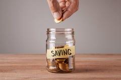 saving Frasco de vidro com moedas e uma economia da inscrição O homem mantém a moeda disponivel imagens de stock royalty free