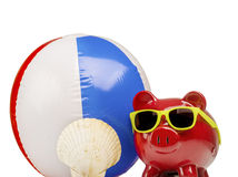Saving for fun holiday vacation. Concept image of piggy bank wearing sunglasses, beach ball and shell Royalty Free Stock Image