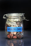 Saving for health care. A jar of money being saved for health care Stock Photos