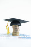 Saving for higher education with Mortarboard on a. Stack of Euro coins and 20 Euro banknotes Stock Photography